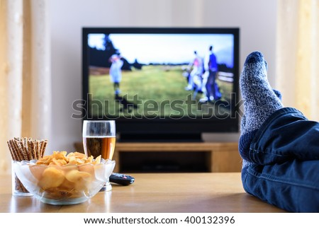 Television, TV watching (golf game) in living room with feet on table - stock photo