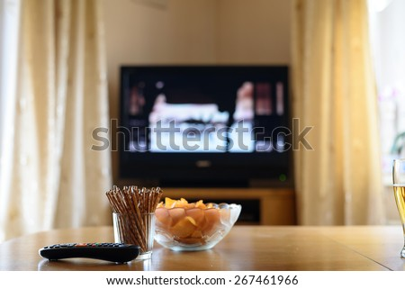 television, TV watching (movie) with snacks lying on table - stock photo