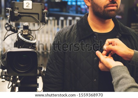 Television video camera recording interview in broadcast news studio. Blurred background. Media, production, TV and broadcast concept