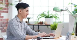 telework concept - sideview of asian man use computer to work and has a video meeting at home