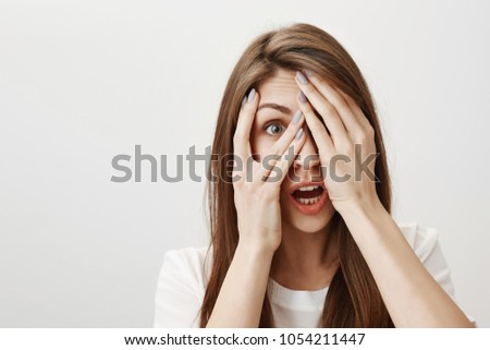Tell me when horror is over. Scared and stunned attractive caucasian girl covering eyes with palms, peeking through fingers and expressing shock and fright, standing with dropped jaw over gray wall #1054211447