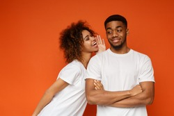 Tell me your secrets. Pleasant smiling african-american woman whispering on ear to her man something important, orange background