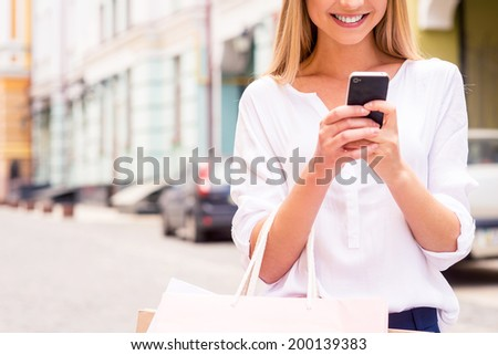 Telling friend about sales. Close-up of beautiful young smiling woman holding shopping bags and mobile phone while standing outdoors - stock photo