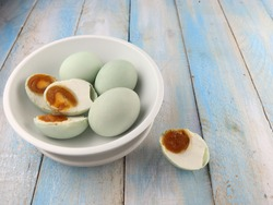 Telur asin or salted duck egg is traditional Indonesian food made by soaking duck eggs in brine and eaten as condiment or as flavoring, served in white bowl on wooden blue table. Selective focus.