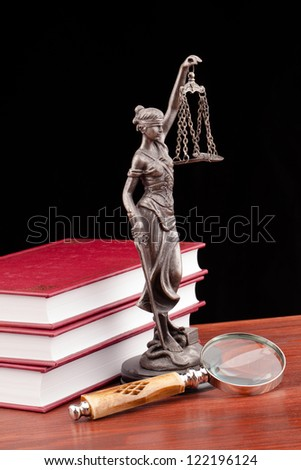 Temida statue on wooden table and black background