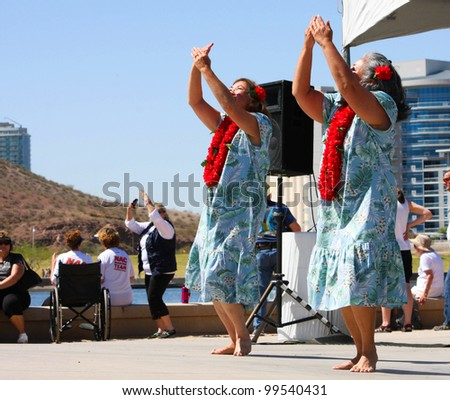 TEMPE, AZ - MARCH 31: Two unidentified women, wear print dress and lei, while they dance to HawIiaan music at the Dragon Boat Festival at Tempe Town Lake, March 31, 2012.