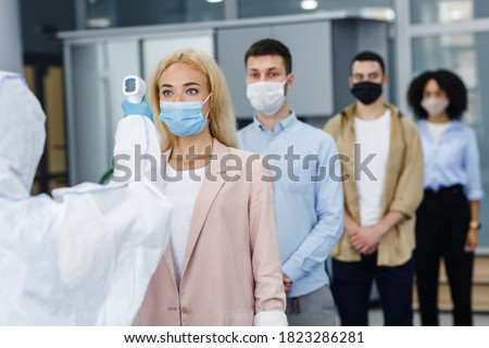 Temperature control test at work and social distancing. Man in protective suit checks multinational workers with non-contact thermometer in morning at entering in office, empty space