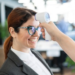 Temperature measurement by infrared electronic digital thermometer to all office workers. Happy woman in a business suit with an electronic thermometer near her forehead. Coronavirus Prevention