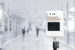 temperature thermometer in hall or shopping mall store indoor blur background and people for scan prevent and protect covid-19 or corona virus before into indoor.