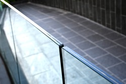 Tempered laminated glass railing balustrade panels frame less ,safety glass for modern architectural buildings. Concept image for exterior path railing and landscape design.