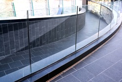 Tempered laminated glass railing of walkway and balcony, frame less balustrade panels, safety glass for modern architectural buildings. Close up detail of film and layer thickness, joint and bolt.