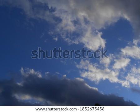 Tempestuous menacing clouds shaped like surreal ghosts dancing in the dark blue sky Foto stock ©