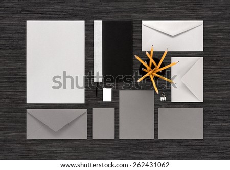 Template for corporate branding identity. Mockup consist of paper, envelopes, business card, notebook, pencils, eraser, binder clip. For design presentations or portfolio. Top view on black table.