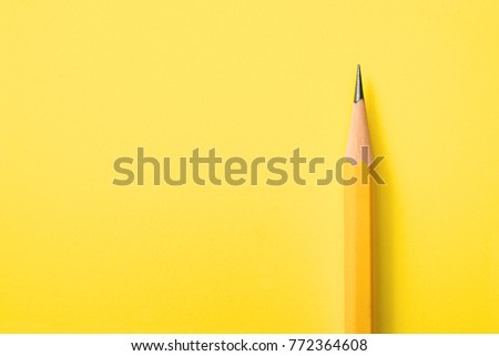 Template with copy space by top view closeup macro photo of wooden yellow pencil put on yellow paper that look minimal and clean. Side flash light made difference between them by highlight and shadow.