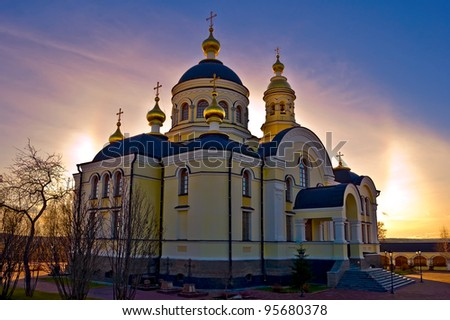 Temple of Righteous Simeon of gold baths, trees against the sunset sky and sun (Simeon the New Compound Tikhvin nunnery in with. Merkushino Verkhotursk district of Sverdlovsk region)
