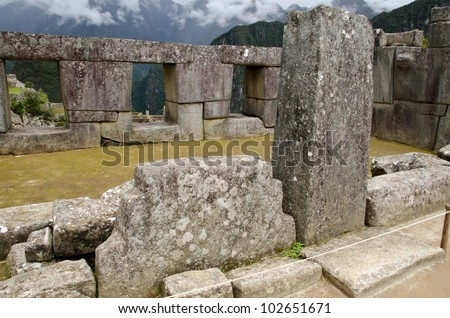 Temple of the three windows on the Sacred Plaza in Machu Picchu, Peru. The column in the front was carved to hold rock lintels. In the foreground, a sacred rock with typical three steps on both sides.