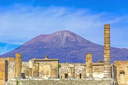 Temple ruins at the ancient Roman city of Pompeii, Italy. which was destroyed by mount Vesuvius (seen in background) volcanic eruption in AD 79