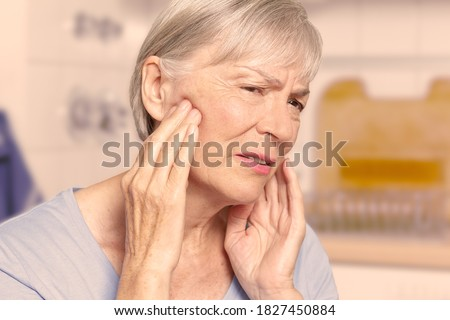 Temporal arteritis: senior woman suffering from painful jaw joints, filter effect. Foto stock ©