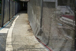 Temporary passageways in construction areas where protective tarpaulins are used for safety and hygiene.