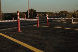 Temporary roadblocks, road repair, road construction. the new road is blocked by a tape, stretched over poles, a lane, asphalt