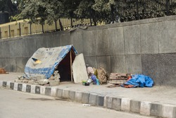 temporary tent of unidentified homeless people on side of street in Delhi, India