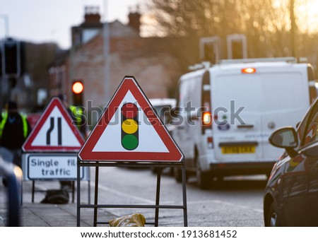 Temporary traffic lights triangle warning sign and traffic light showing red stop signal in background with queuing traffic jam at roadworks on sunny summer day ストックフォト ©