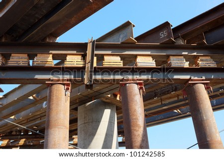Temporary wood bracing and shims, large diameter pipes and structural steel support roadway beams before concrete is poured on bridge construction project