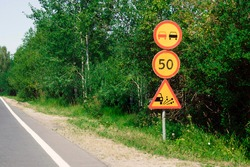 Temporary yellow warning and prohibiting road signs in bushes on side of rural road. Three traffic signs, warning traffic sign, signals on country road, sign for release of gravel from under wheels.