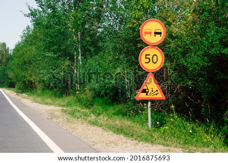 Temporary yellow warning and prohibiting road signs in bushes on side of rural road. Three traffic signs, warning traffic sign, signals on country road, sign for release of gravel from under wheels. ストックフォト ©