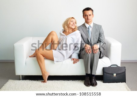 Tempting woman in male shirt trying to seduce her husband persuading him to stay at home