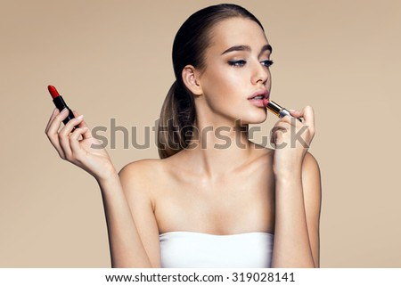 Tempting young woman with  lipstick / photography of mixed race Latina Brazilian brunette smiling girl on beige background
