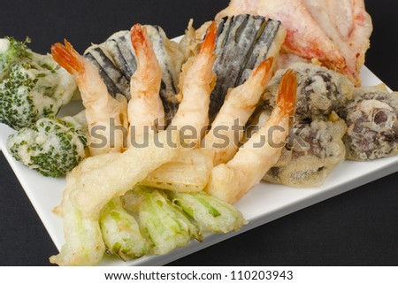 Tempura - Japanese deep fried prawns and assorted vegetables (shiitake mushrooms, peppers, spring onions, aubergine, broccoli and bamboo shoots) on a black background.