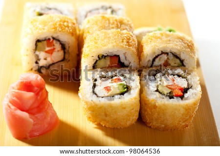 Tempura Maki Sushi - Deep Fried Roll made of Crab Meat, Paprika and Lettuce inside. Served on Wooden Plate