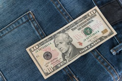 Ten American dollars bill sticking out of the blue jeans pocket,Pocket in old jeans jacket with ten US dollar,Business concept exchange