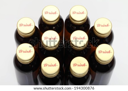 Ten bottles grouped together with identical bottle caps.