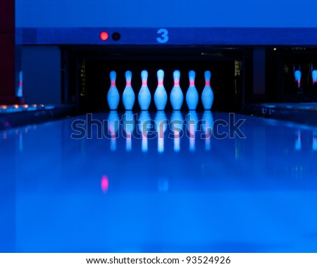 Ten bowling pins at the end of alley. Ultraviolet luminosity