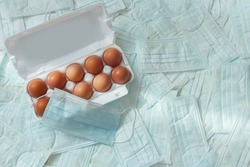 Ten brown eggs in white box on the background of respiratory protection medical masks. Concept of canceling the Easter holiday during the global pandemic. Flat lay, top view, copy space.