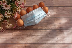 Ten brown eggs, medical masks and flowers on wooden background. Concept of canceling the Easter holiday during the global pandemic. Flat lay, top view, copy space.