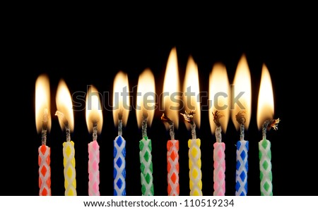 Ten burning candles on black background