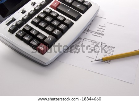 Ten key calculator, financial statement and pencil