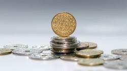 Ten Kroner coin standing on a stack of mixed Danish coins with selective focus. The krone is the official currency of Denmark, Greenland, and the Faroe Islands, introduced on 1 January 1875.