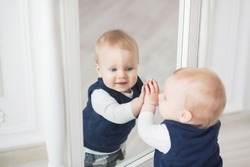 Ten month baby boy stands before the mirror and play with himself