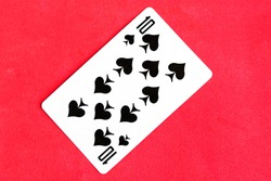 Ten of Spades playing card, red background.