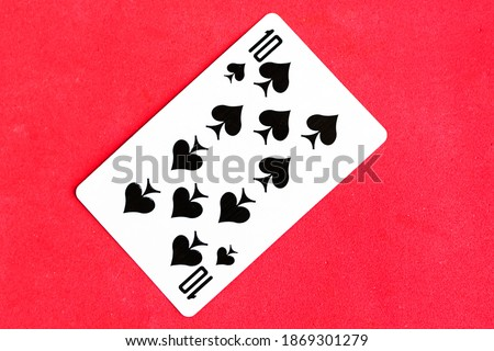 Photo of  Ten of Spades playing card, red background.