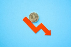 ten rouble coin on blue background with red arrow down. exchange rate chart. ruble depreciation. Exchange rate of rouble fall. Rouble to dollar