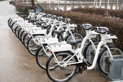 Ten same white rental bicycles at bicycle parking at rainy street