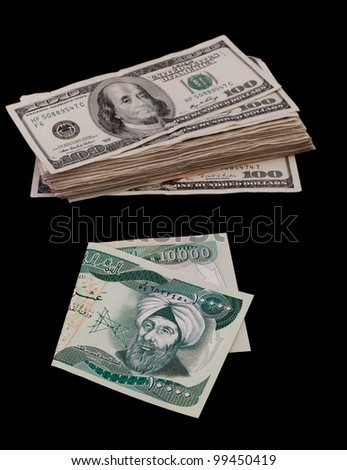 ten thousand Iraqi dinar bill and a bunch of hundred dollar bills isolated on a black background