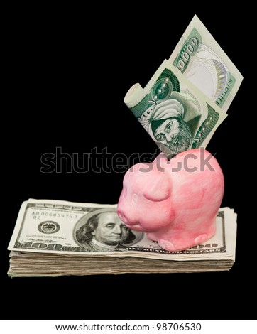 ten thousand Iraqi dinar bill in a pink piggy bank and a bunch of hundred dollar bills isolated on a black background - stock photo