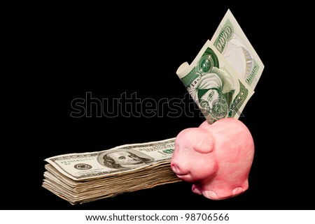 ten thousand Iraqi dinar bill in a pink piggy bank and a bunch of hundred dollar bills isolated on a black background
