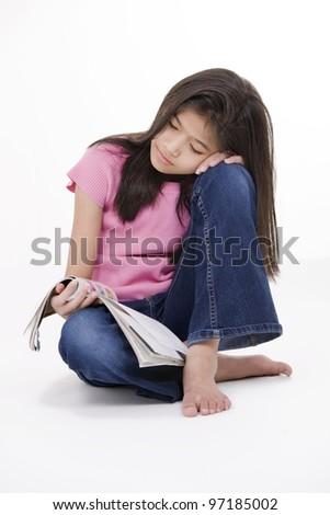 Ten year old Asian girl sitting on floor reading a magazine, isolated on white - stock photo